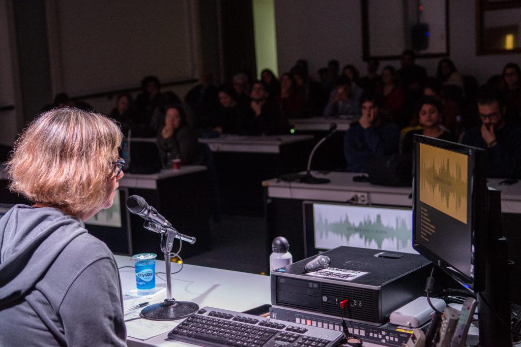 Magda Ruschel fala na XVI Semana da Imagem na Comunicação na Unisinos. A fotografia mostra Magda de lado, o microfone e o computador em sua frente, onde ela controla a apresentação exibida. A apresentação mostra um espectro de áudio. Ao fundo, desfocado, o público que assiste sua exposição.